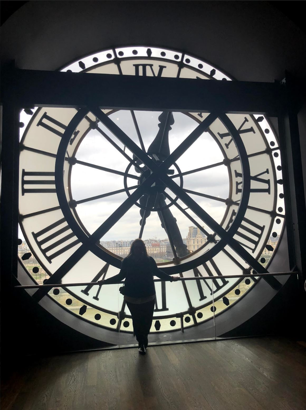 Madison Cline looking outside of clock window in Paris, France