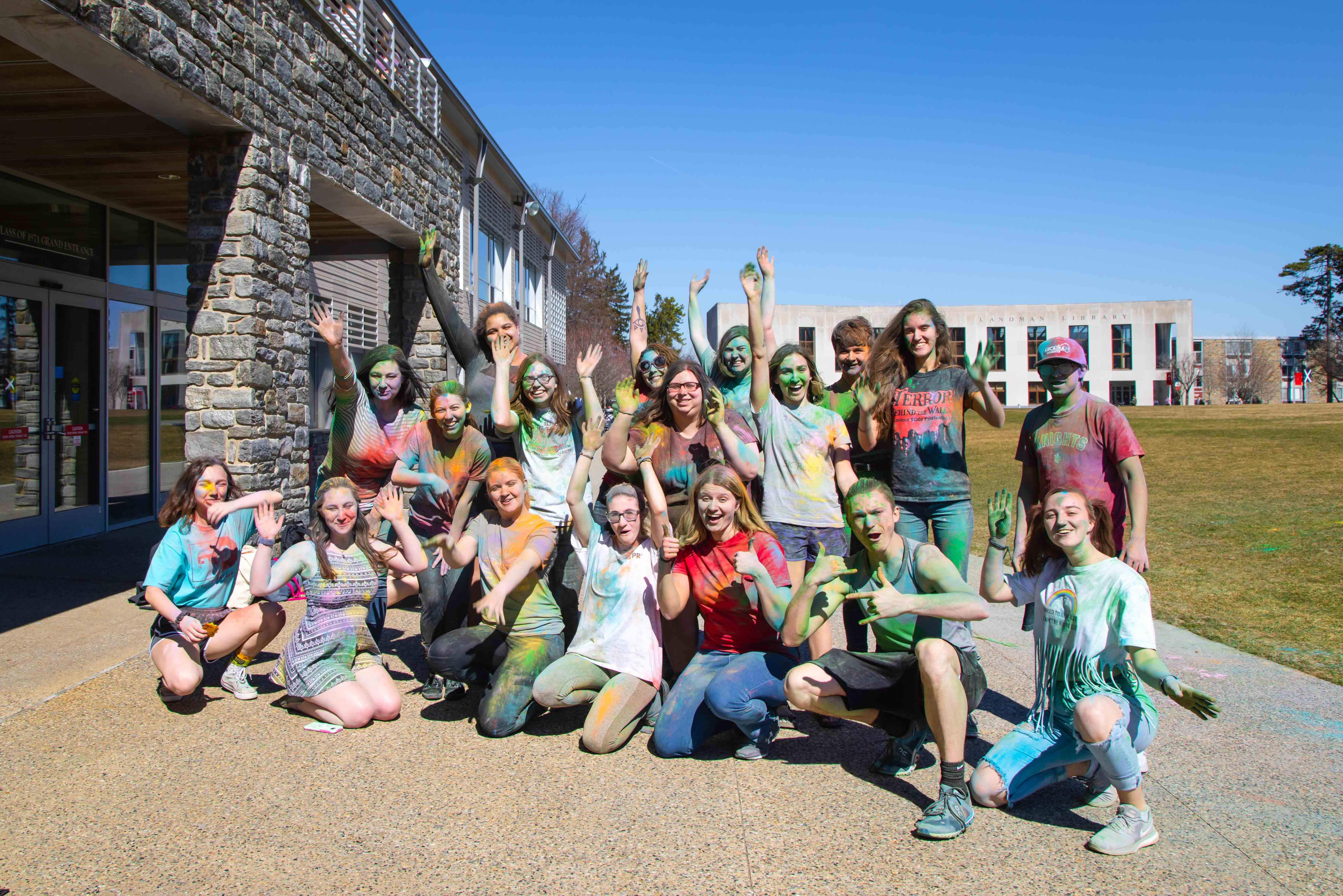 Group of student posing happily covered in color powder on Haber Green
