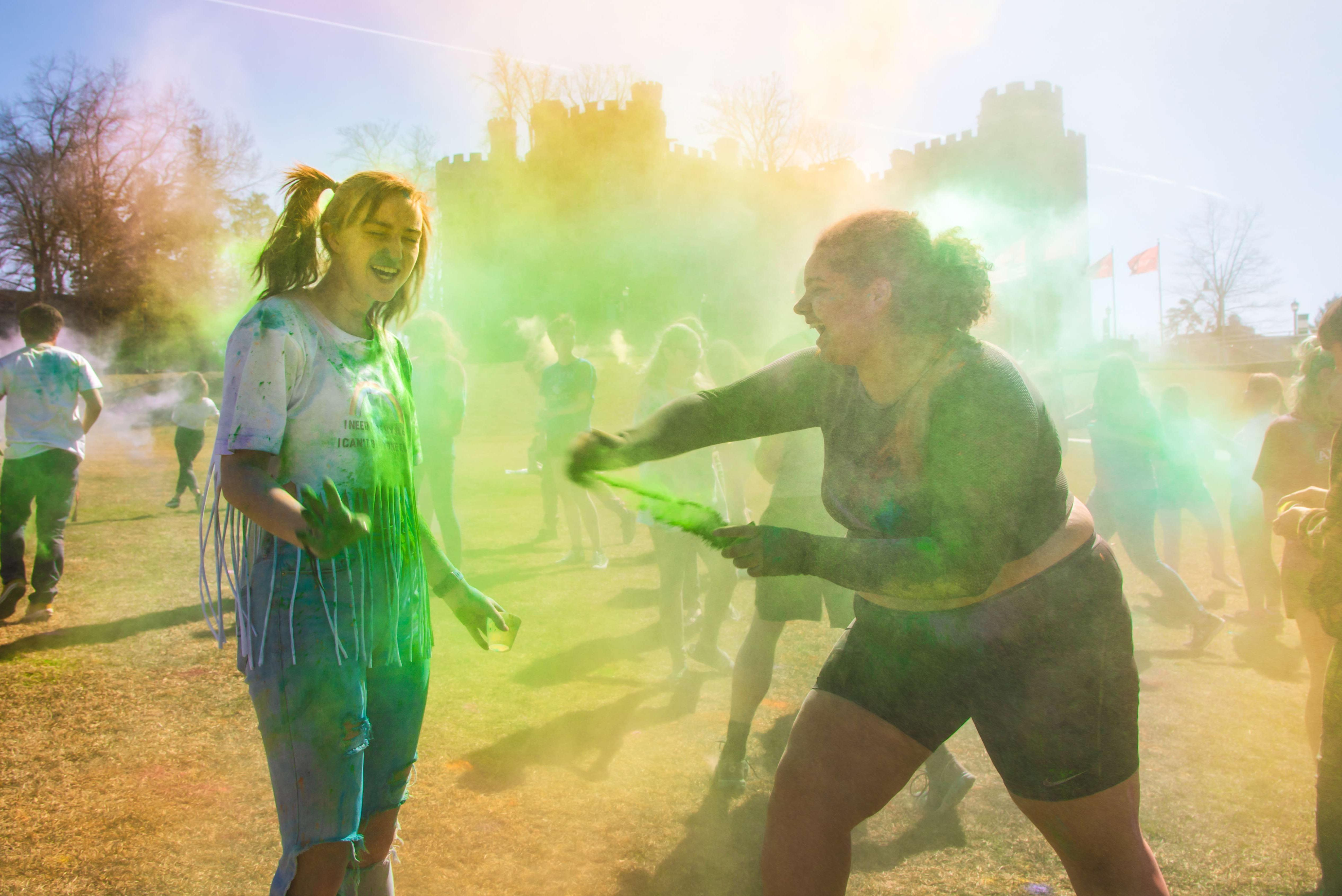 Two female students throw color powder at each other on Haber Green
