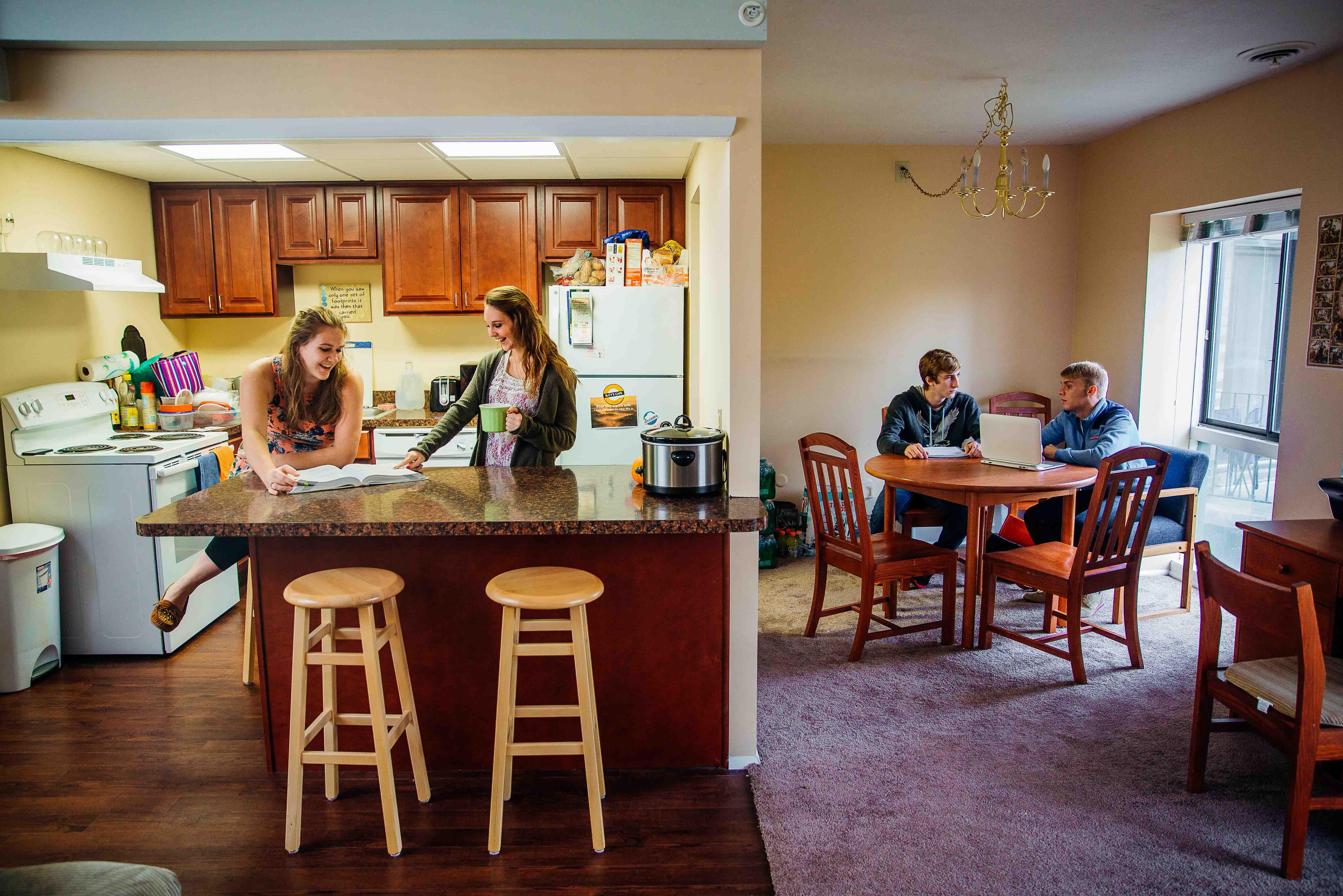 Two female student talk in kitchen while two male students sit at table.