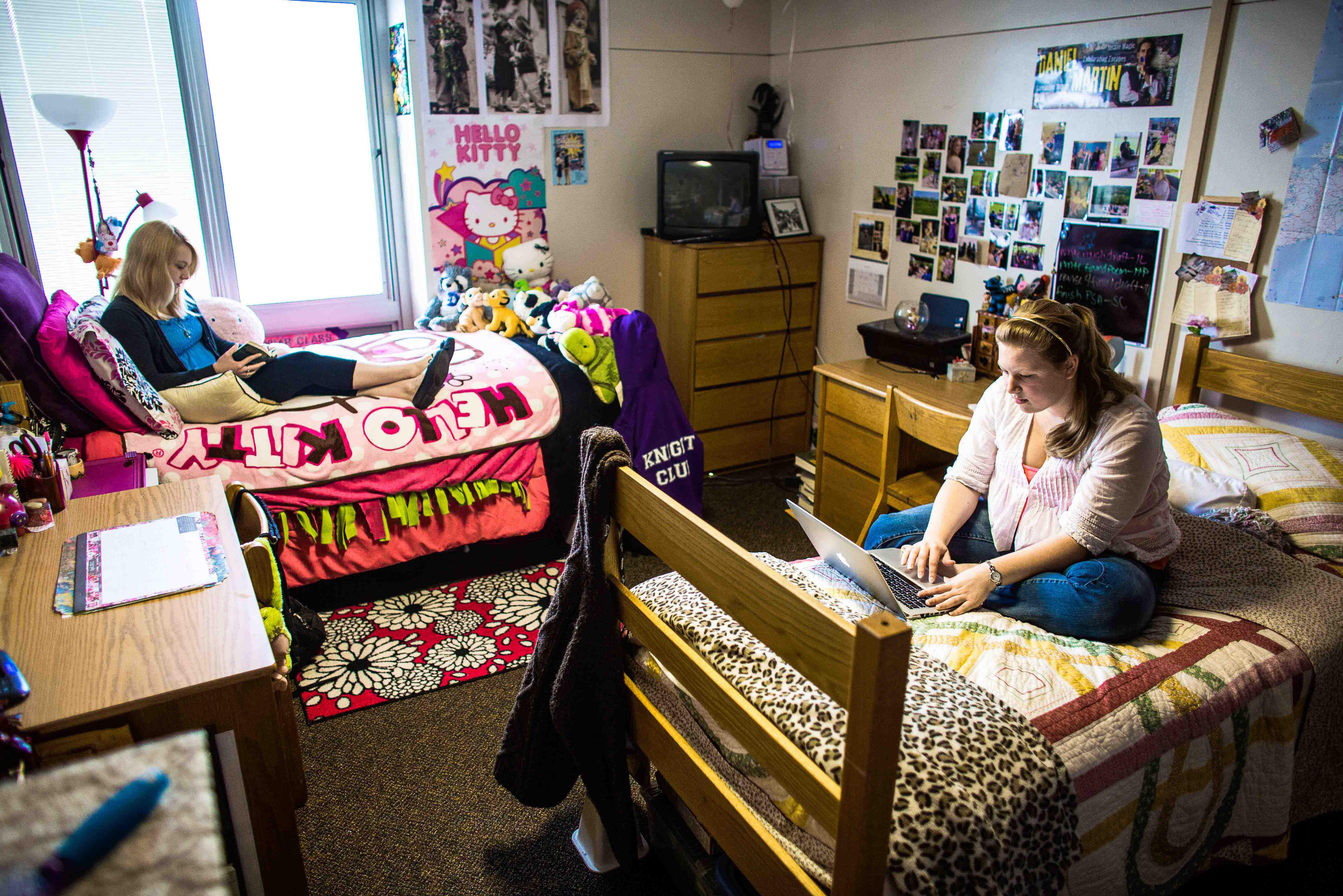 Two female students sitting on their beds working in their dorm room.