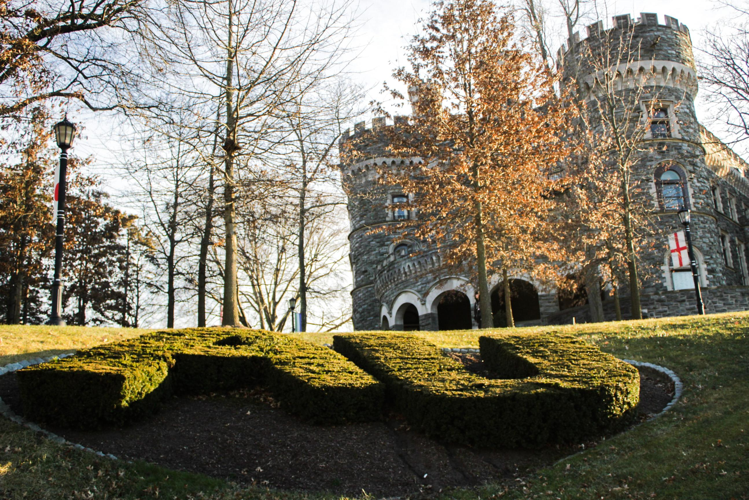 """Grey Towers Castle on Haben Green, in front of """"AU"""" hedges."""