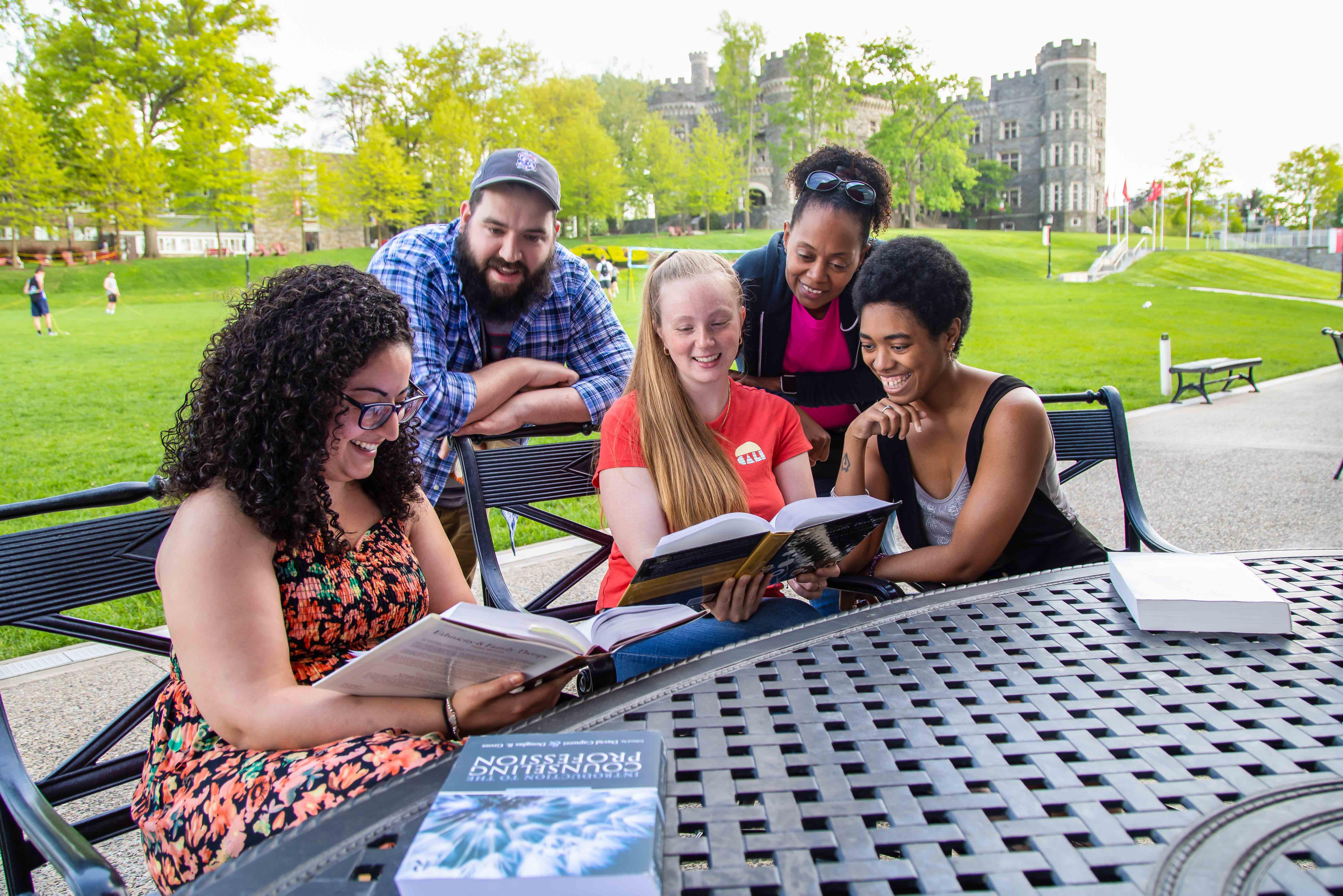 Four female students and one male student reading outside the commons.
