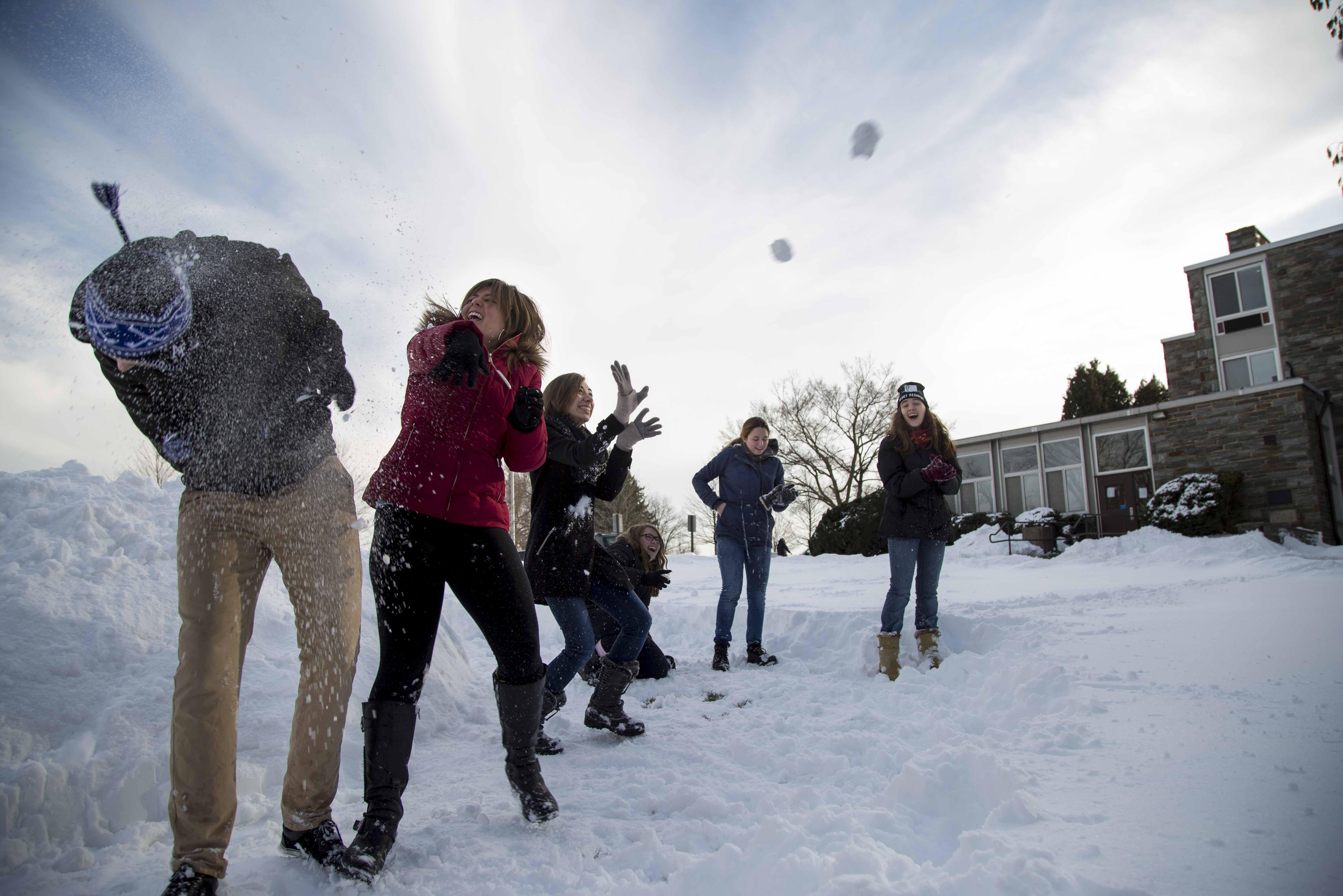 Students having a snowball fight outside of dorms.