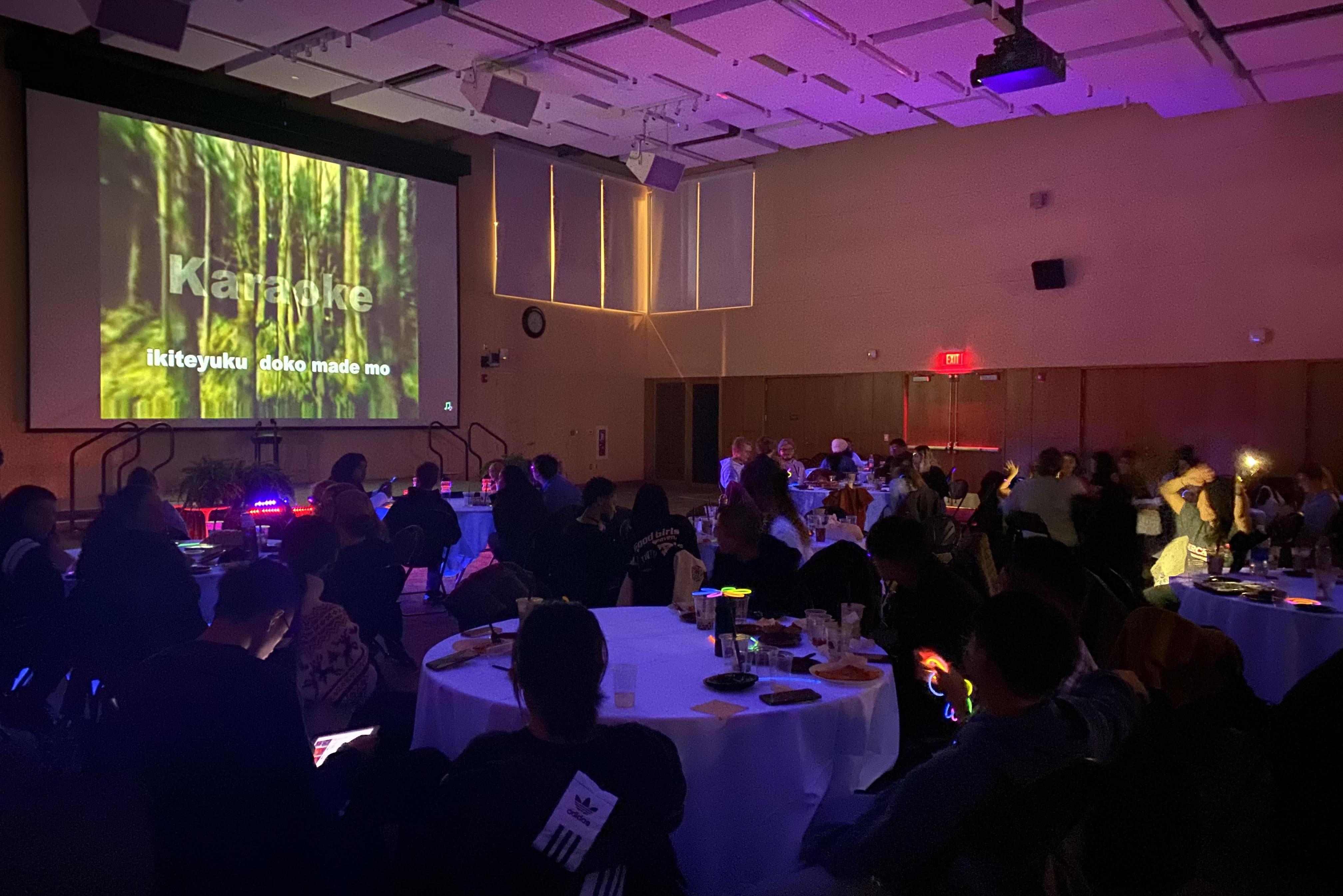 Great room filled with tables and students during glow karaoke party.