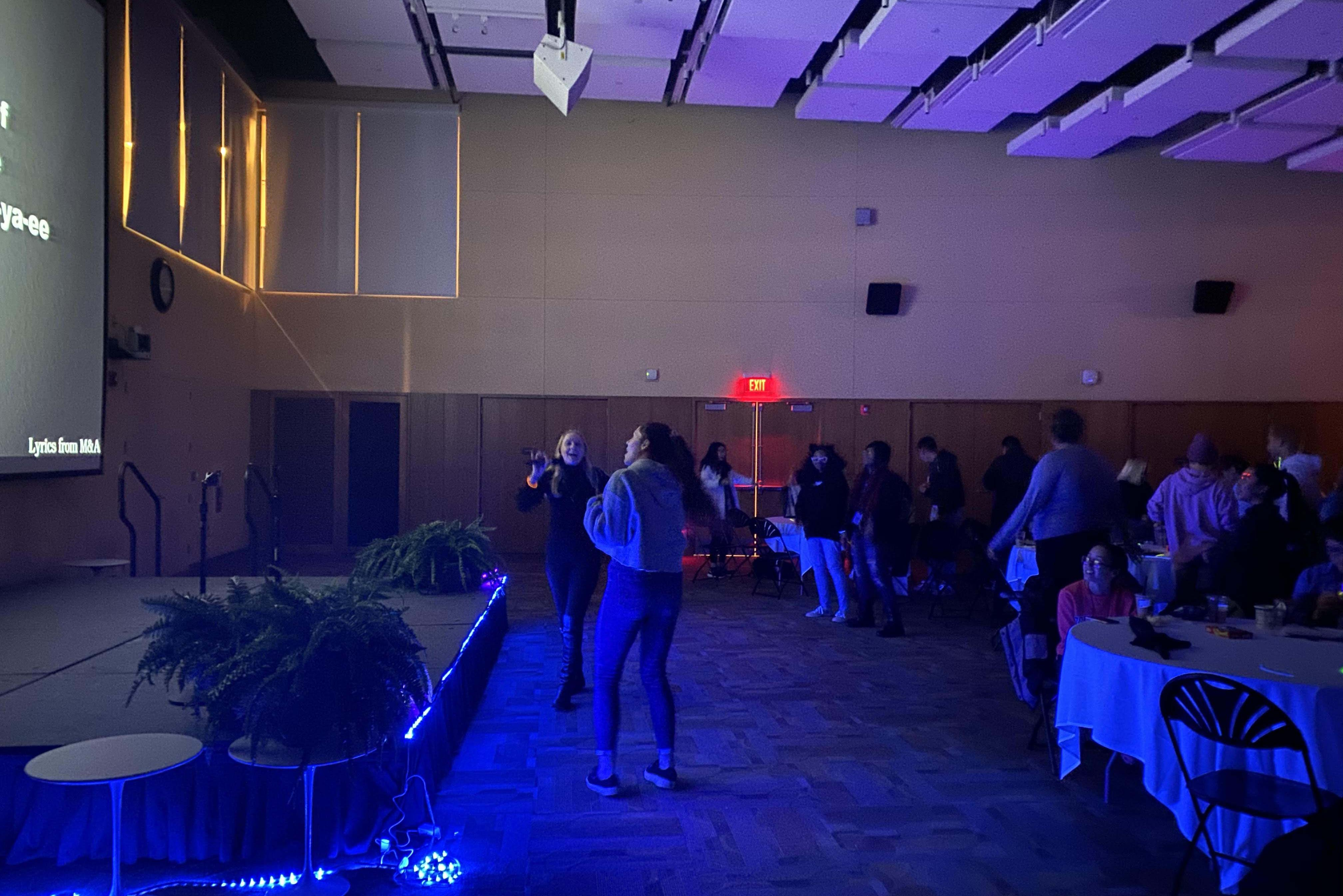 Two female students singing in Great Room during Karaoke Glow Party.