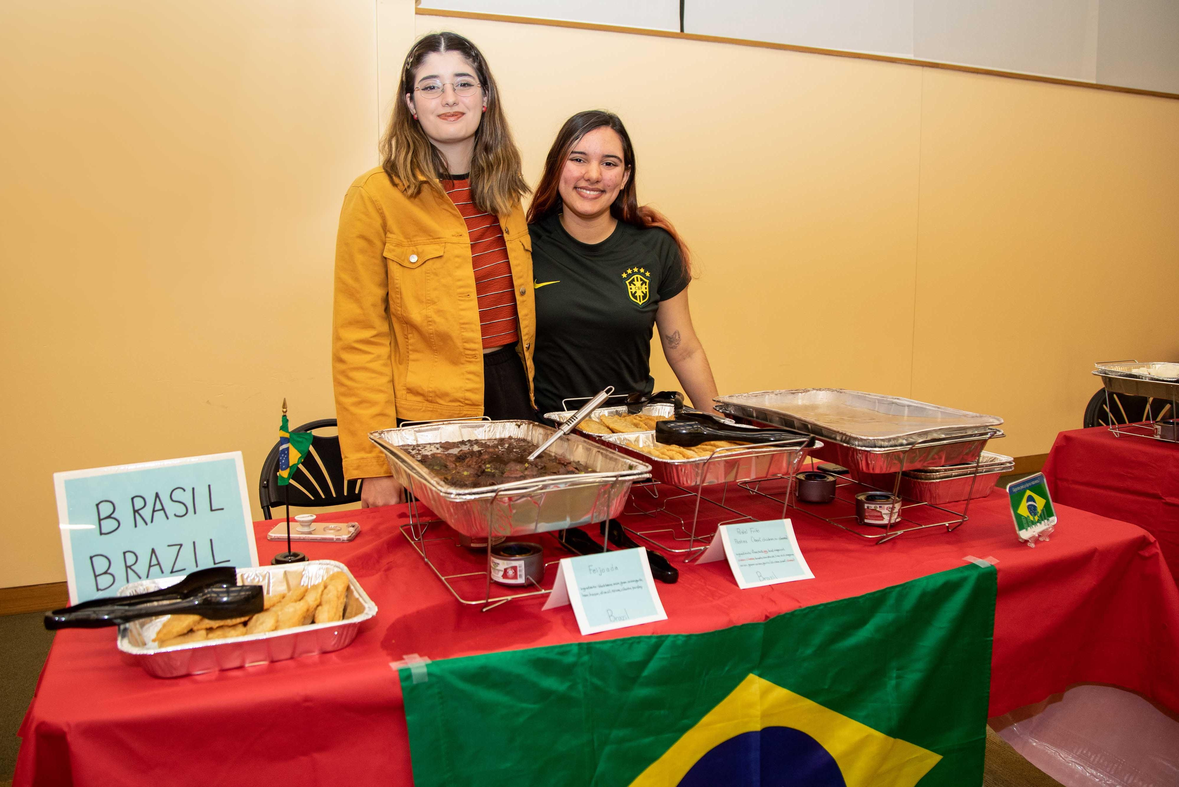 Two female students standing behind Brazil table at Celebrating Cultures event.