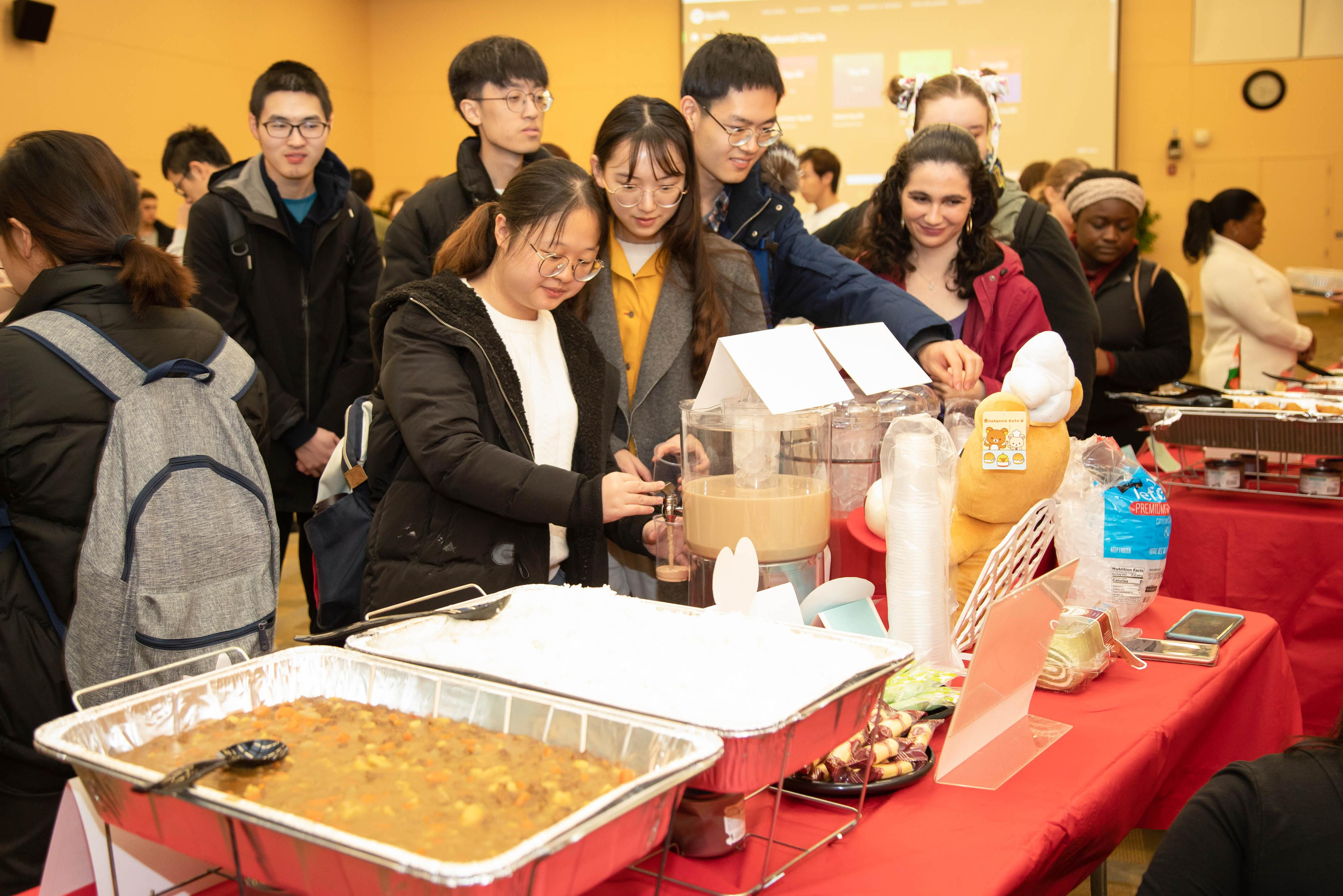 Group of students get food from a buffet table during Celebrating Cultures event