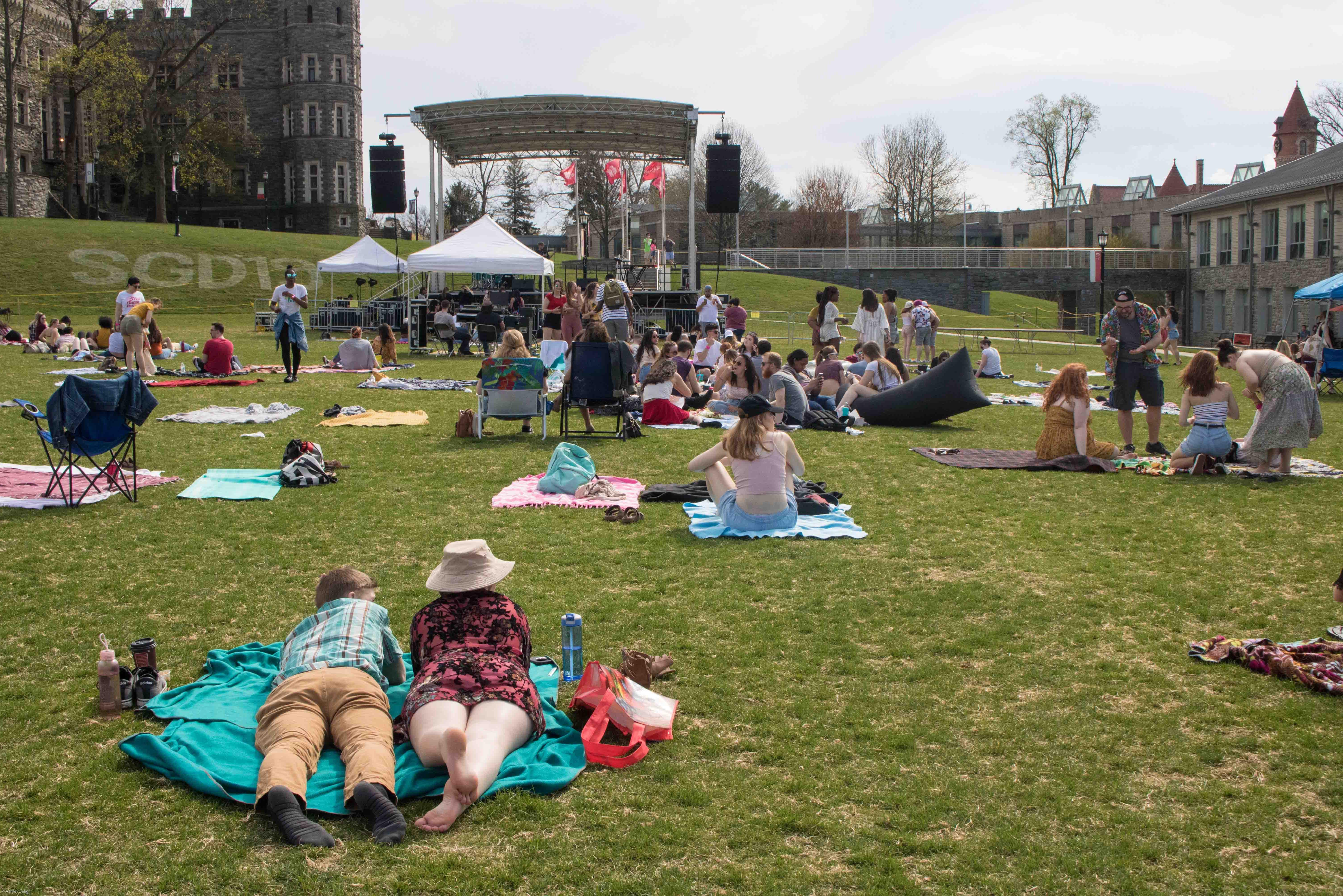 Students lay on blankets on the green while watching a performance at Woodstock.