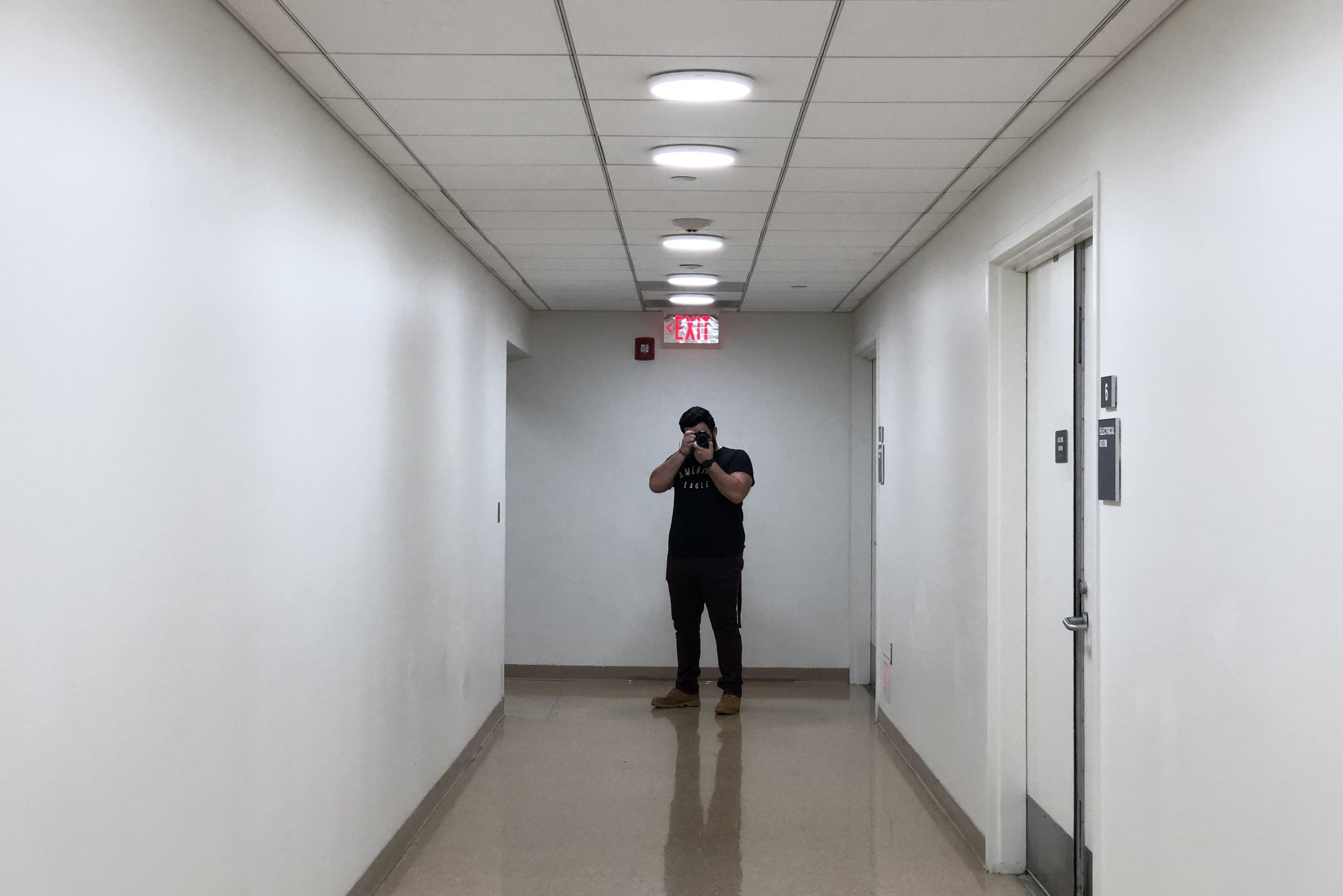 View of a long hallway with a student standing and holding a camera at the end.