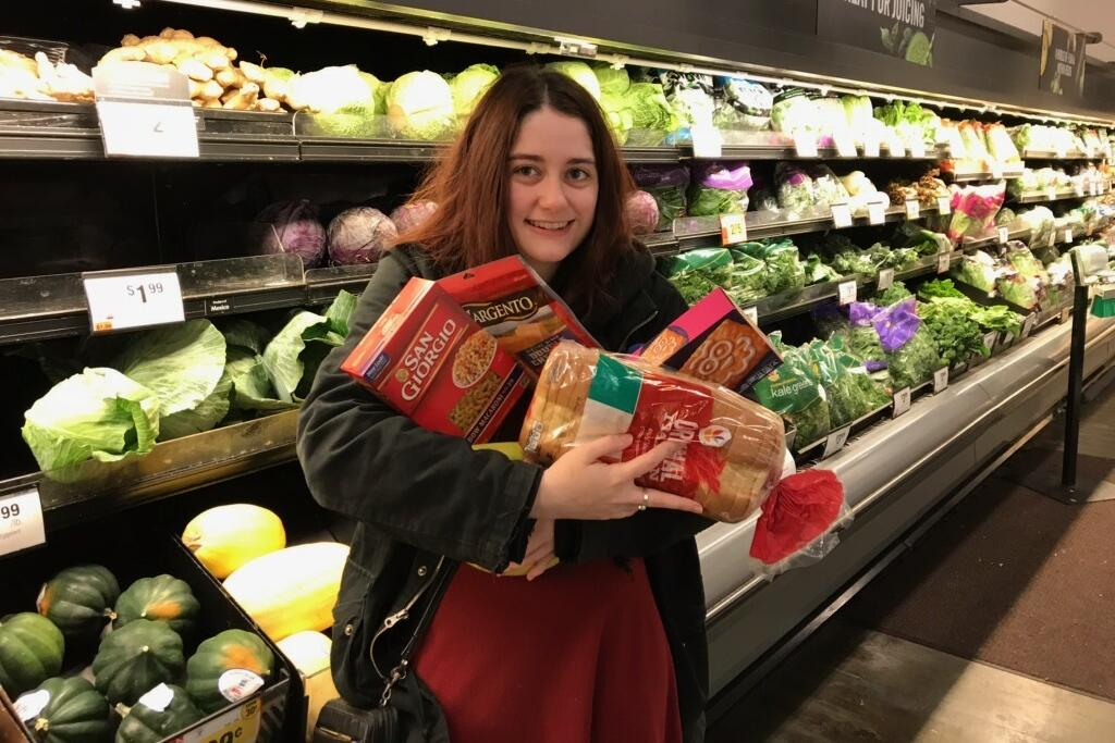 Female student holding a bunch of groceries in a front of produce aisle in store