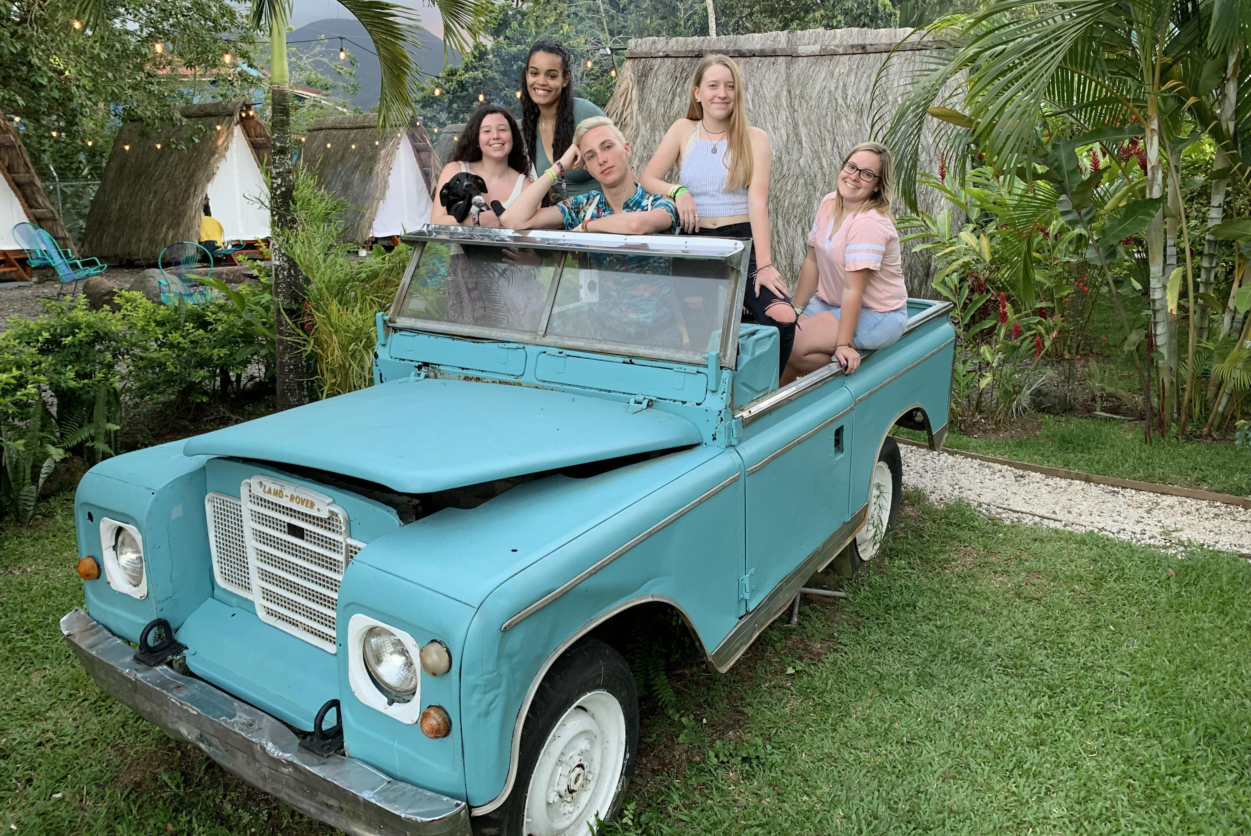 Five students in a teal vehicle in Costa Rica