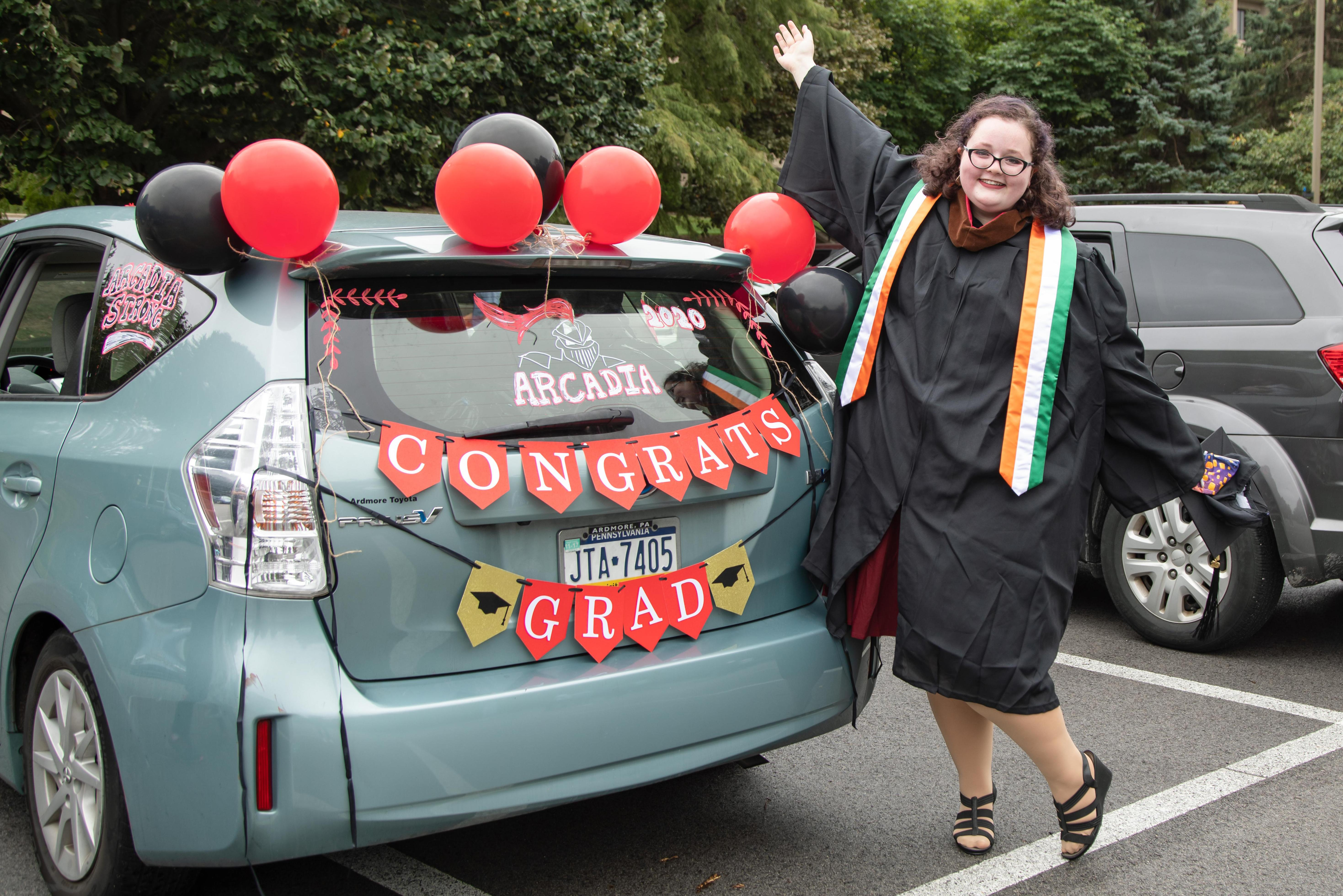 Arcadia University grad in front of decorated hatchback for celebration event