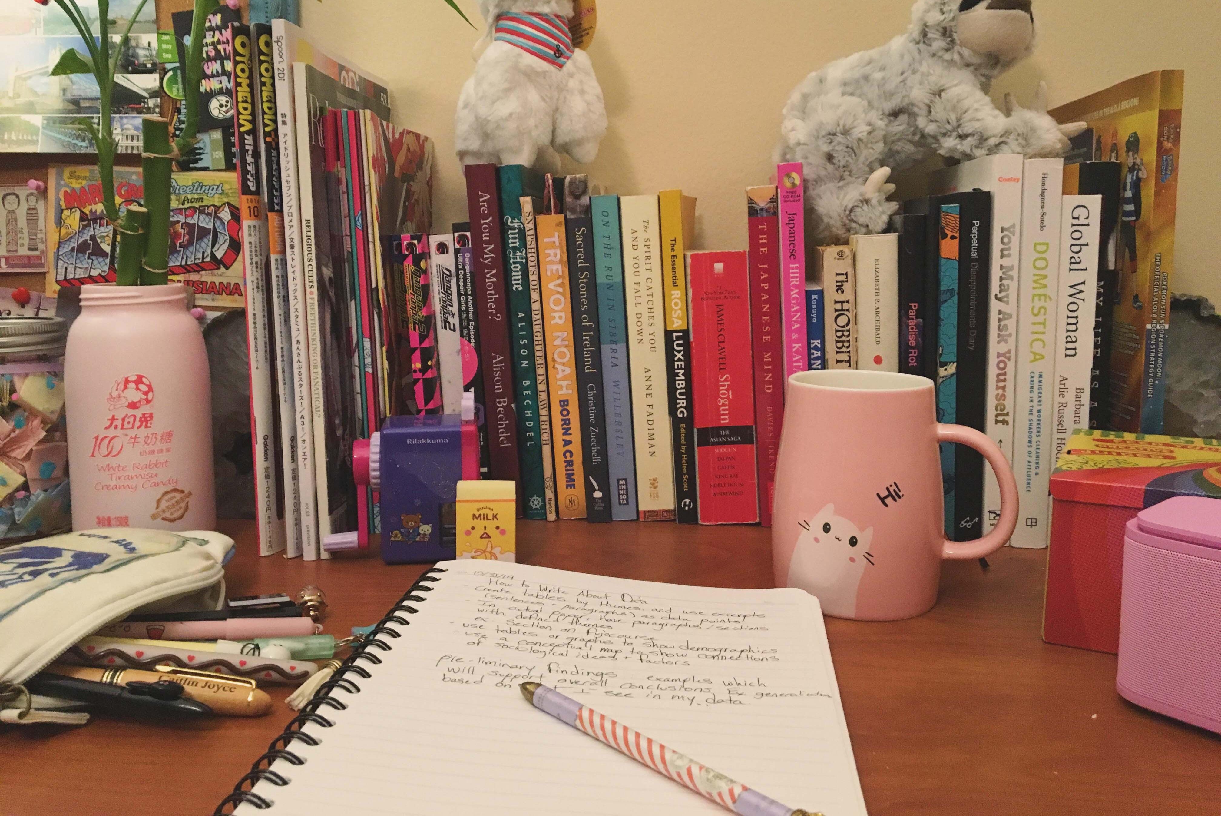 Image of a notebook sitting on a desk with a row of books in the background.