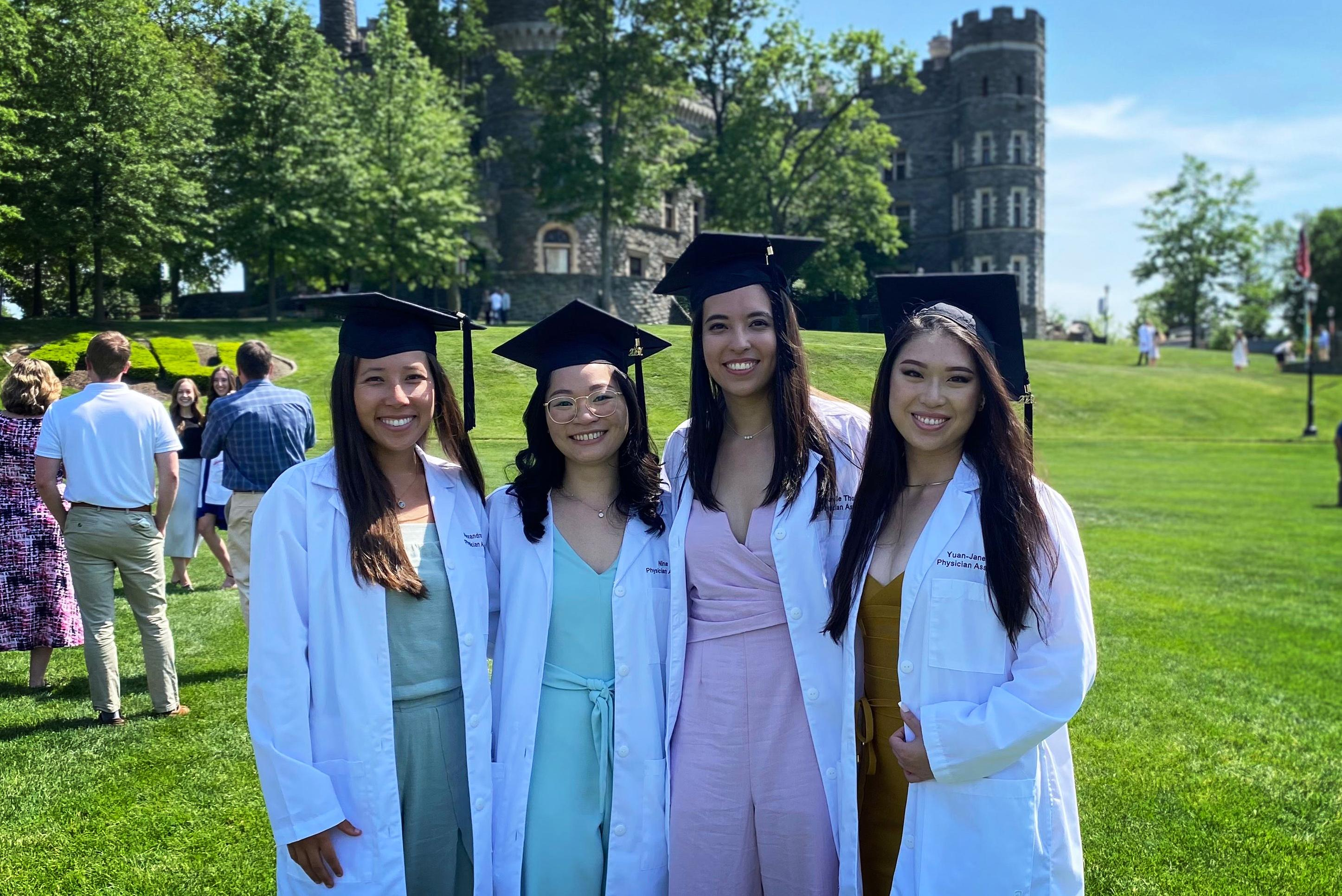 Four female physician assistant graduates with castle behind