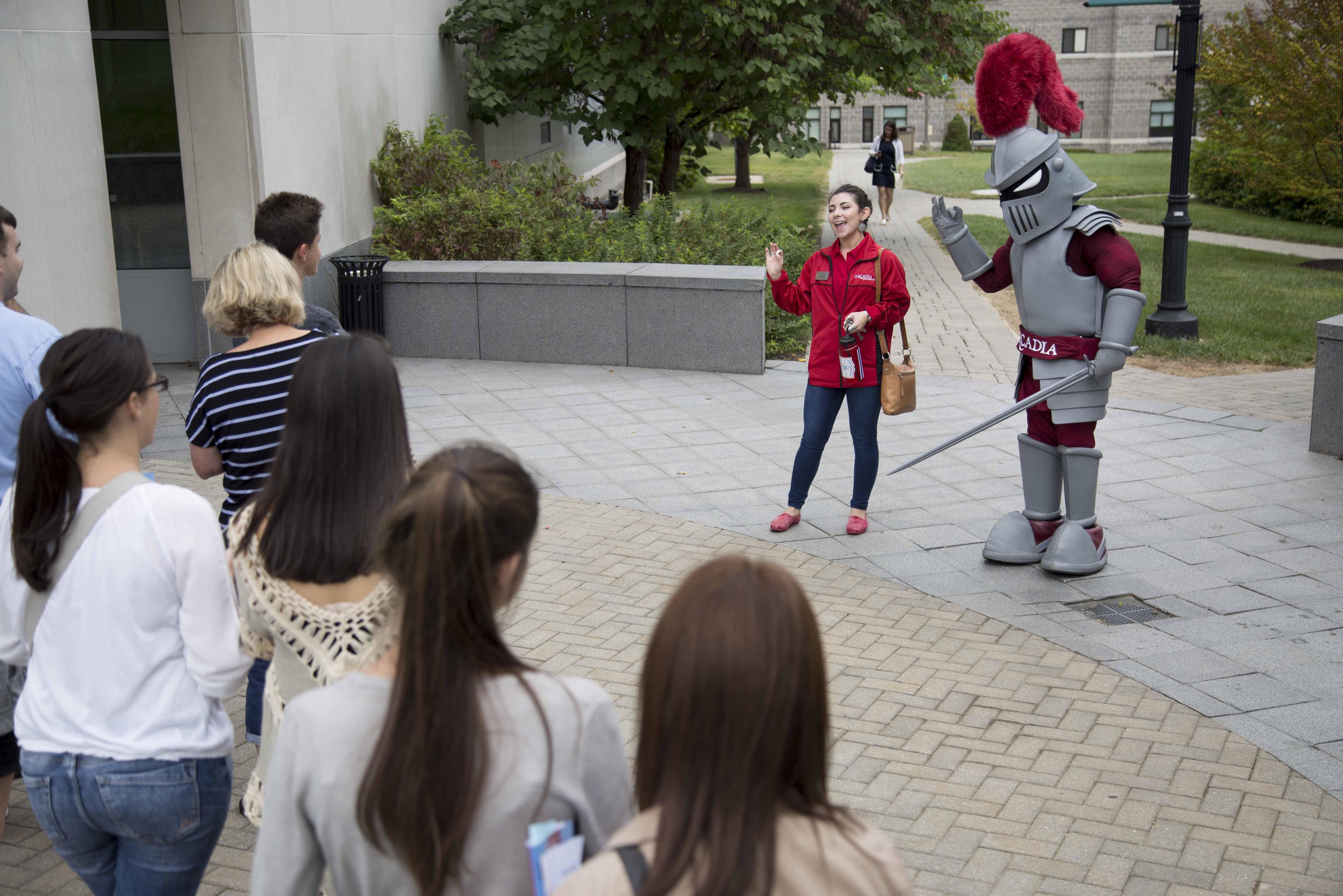 Female ambassador and Knight lead tour group through campus.