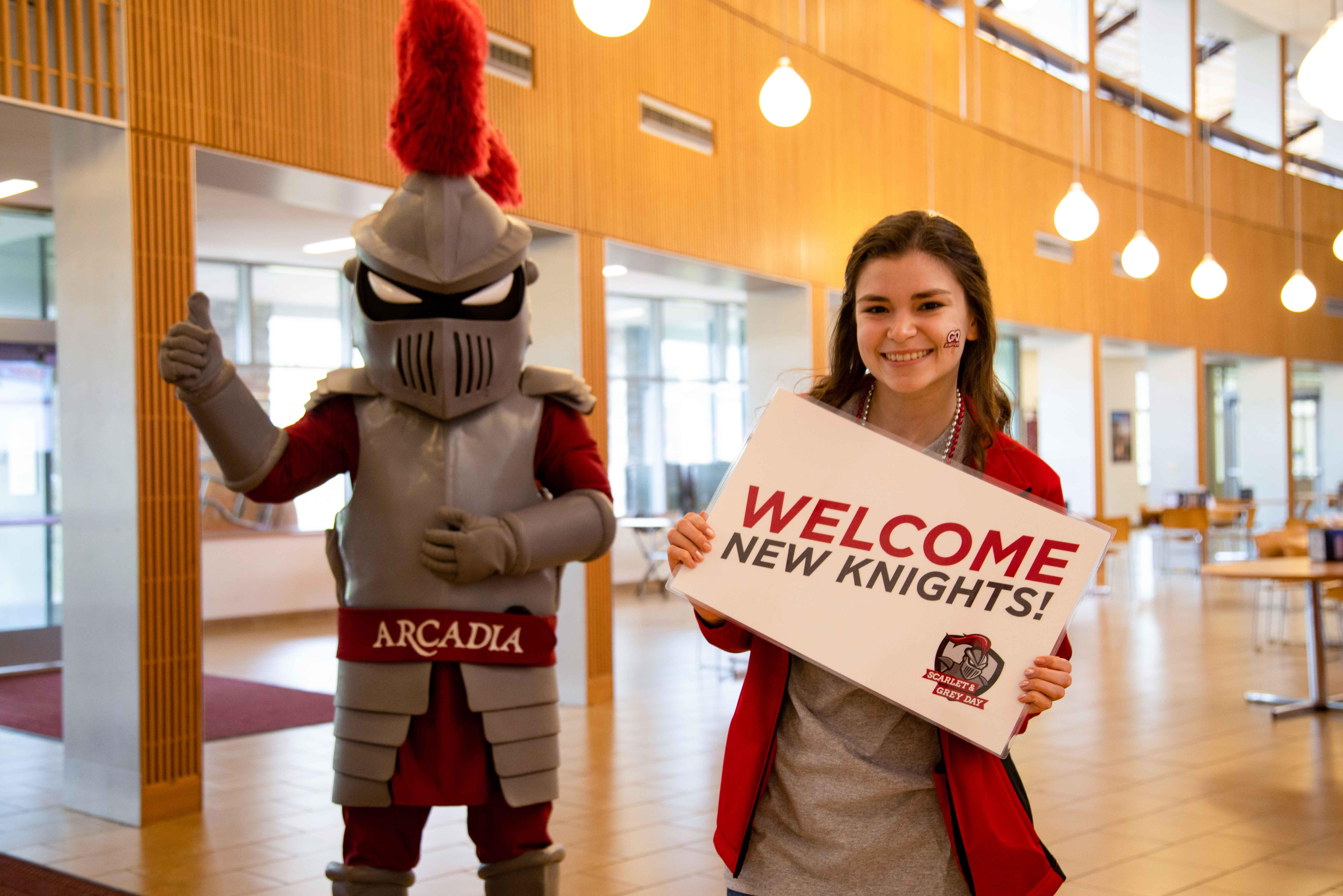 Female student holds welcome new knights sign in commons with knight behind her.