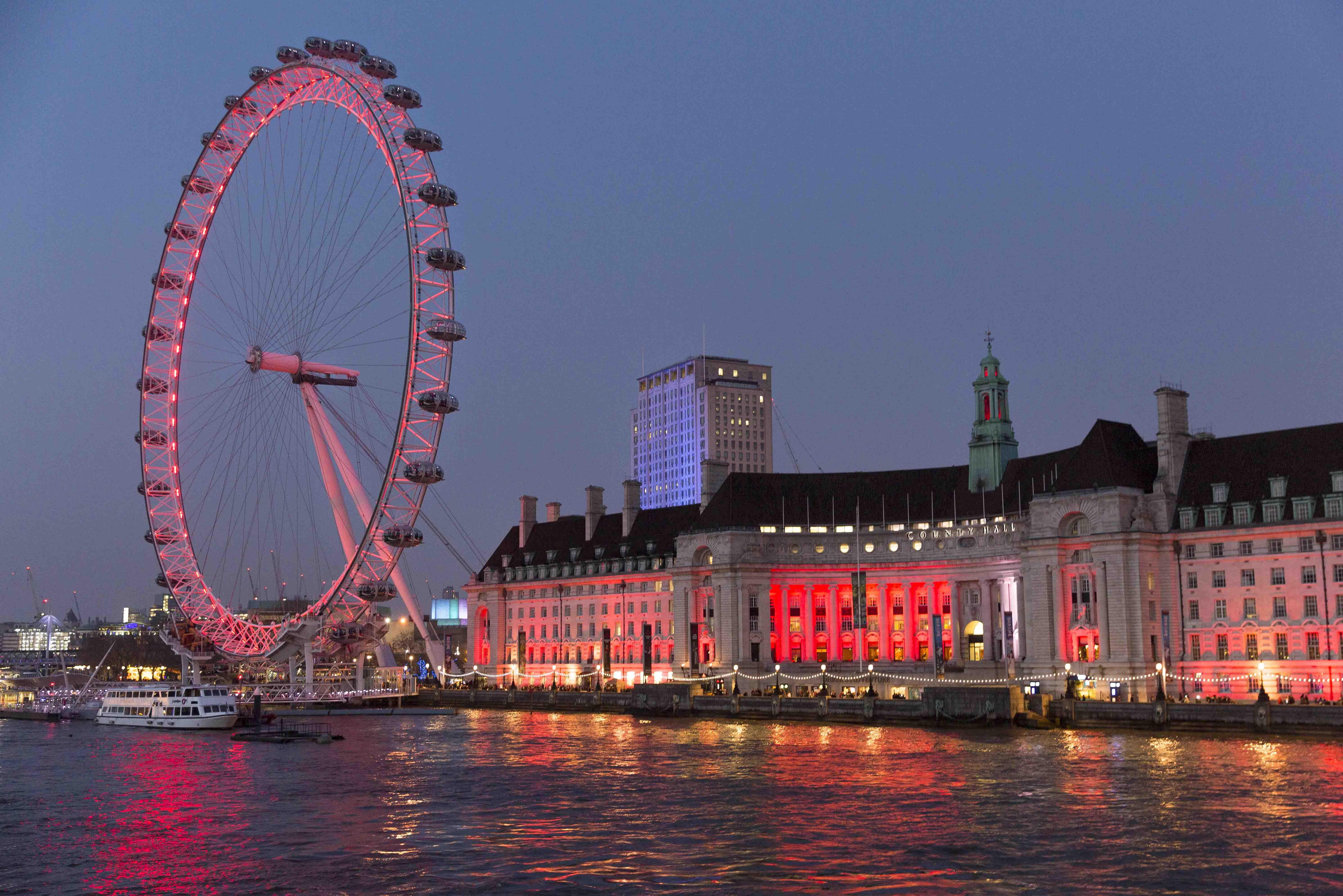 View of the London Eye and city skyline at night.