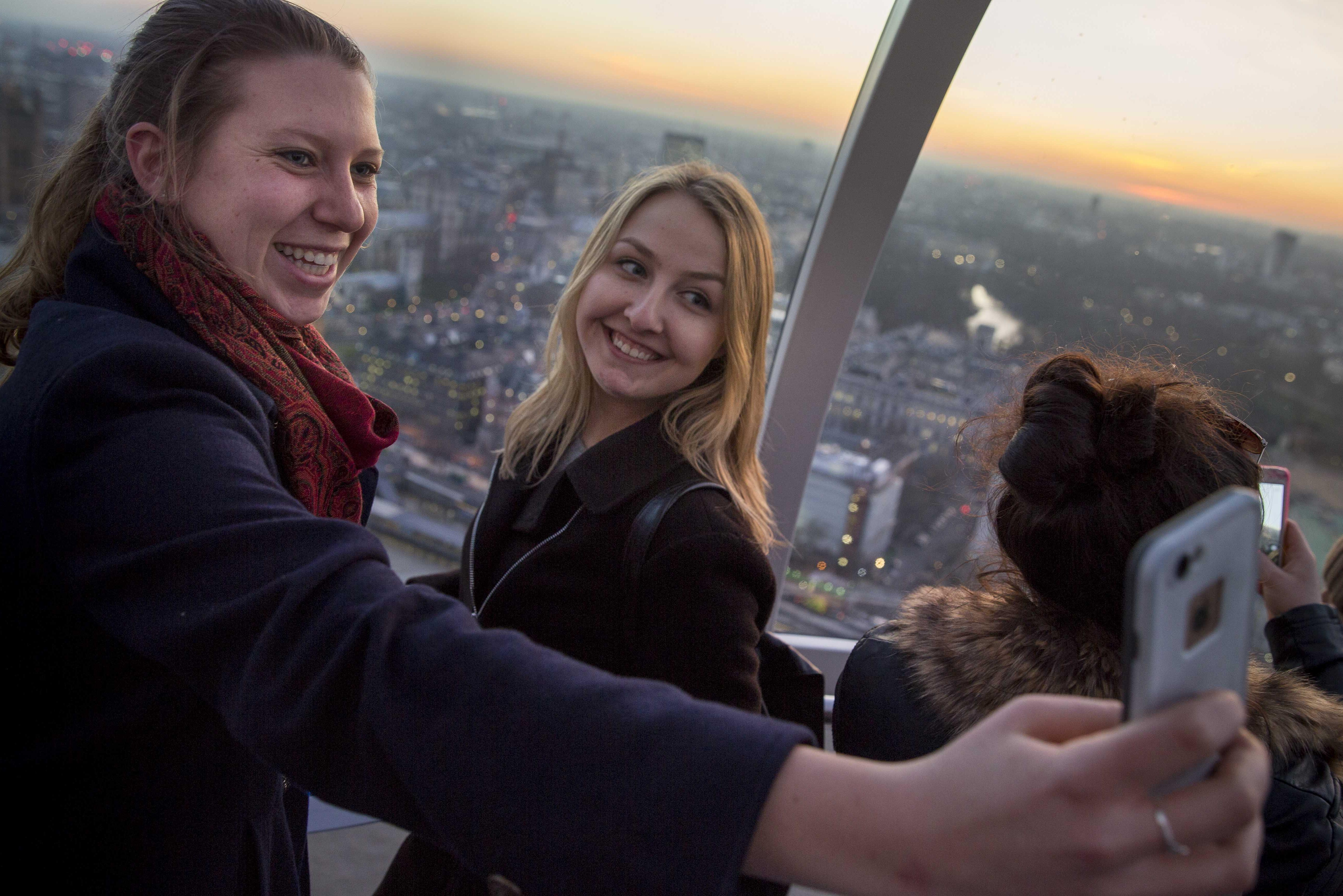 Two female students holding up a cell phone to take a picture on the London eye.