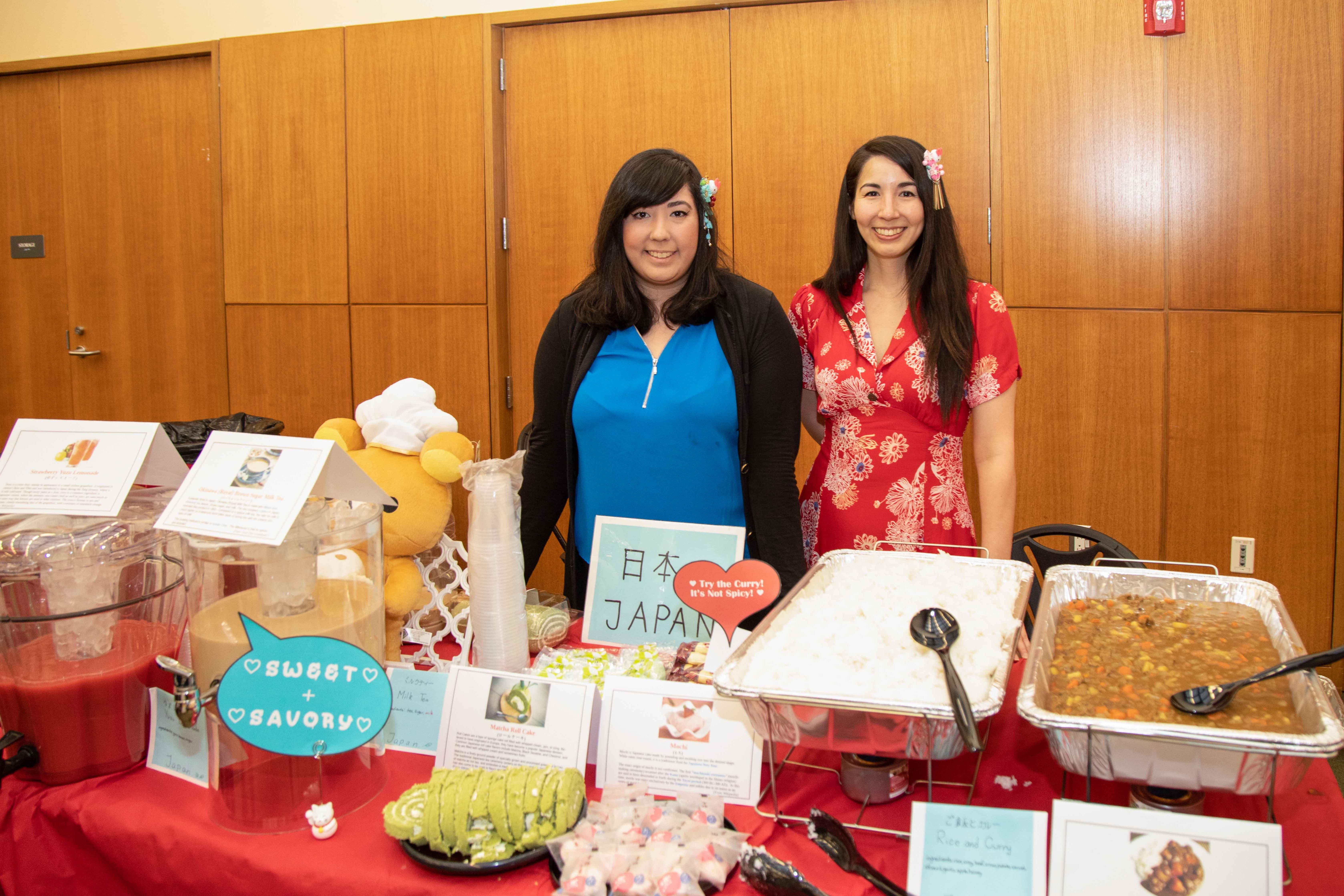 Two female students stand a the Japan table during celebrating cultures.