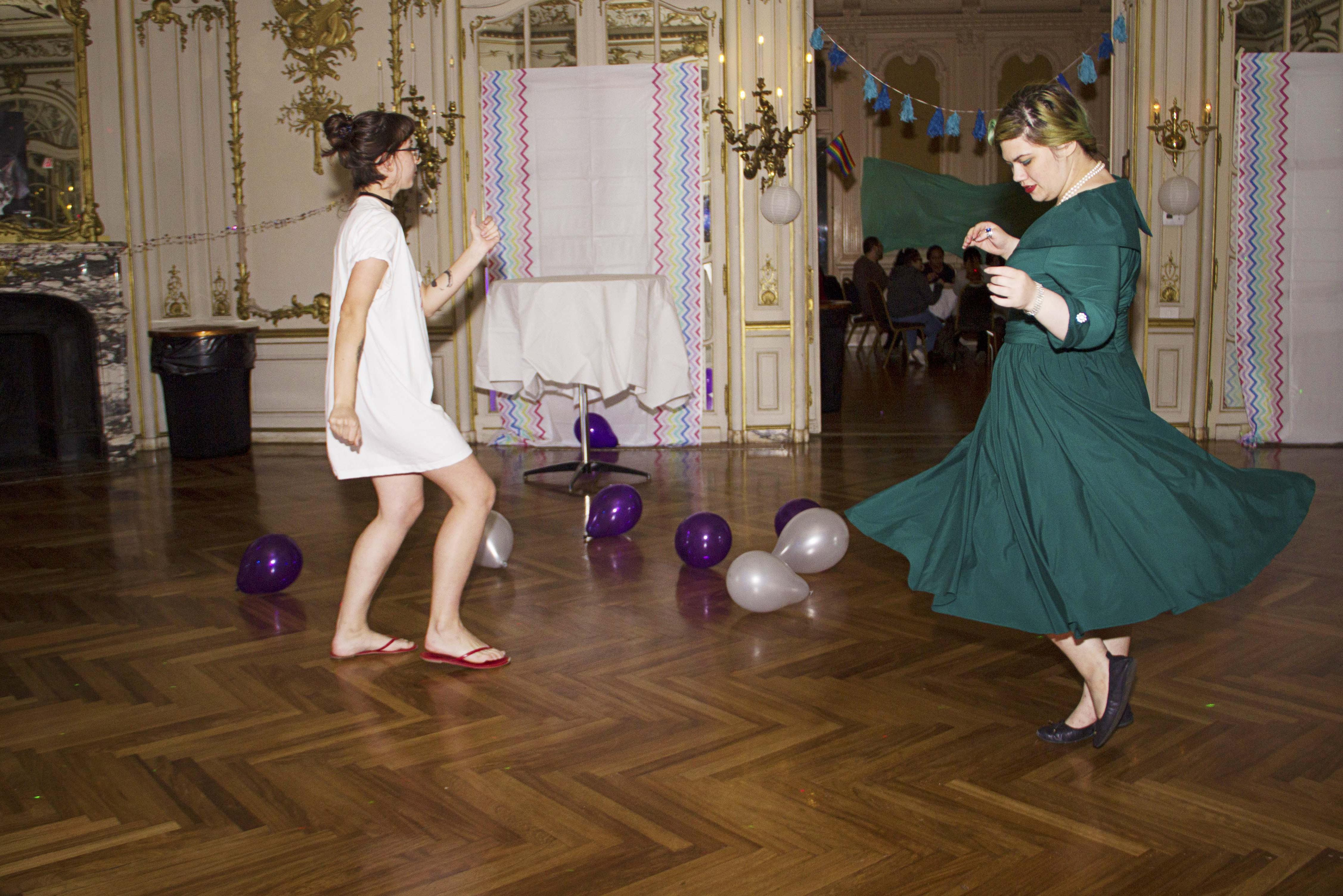 Two students wearing dresses dancing in the mirror room during PRIDE prom.