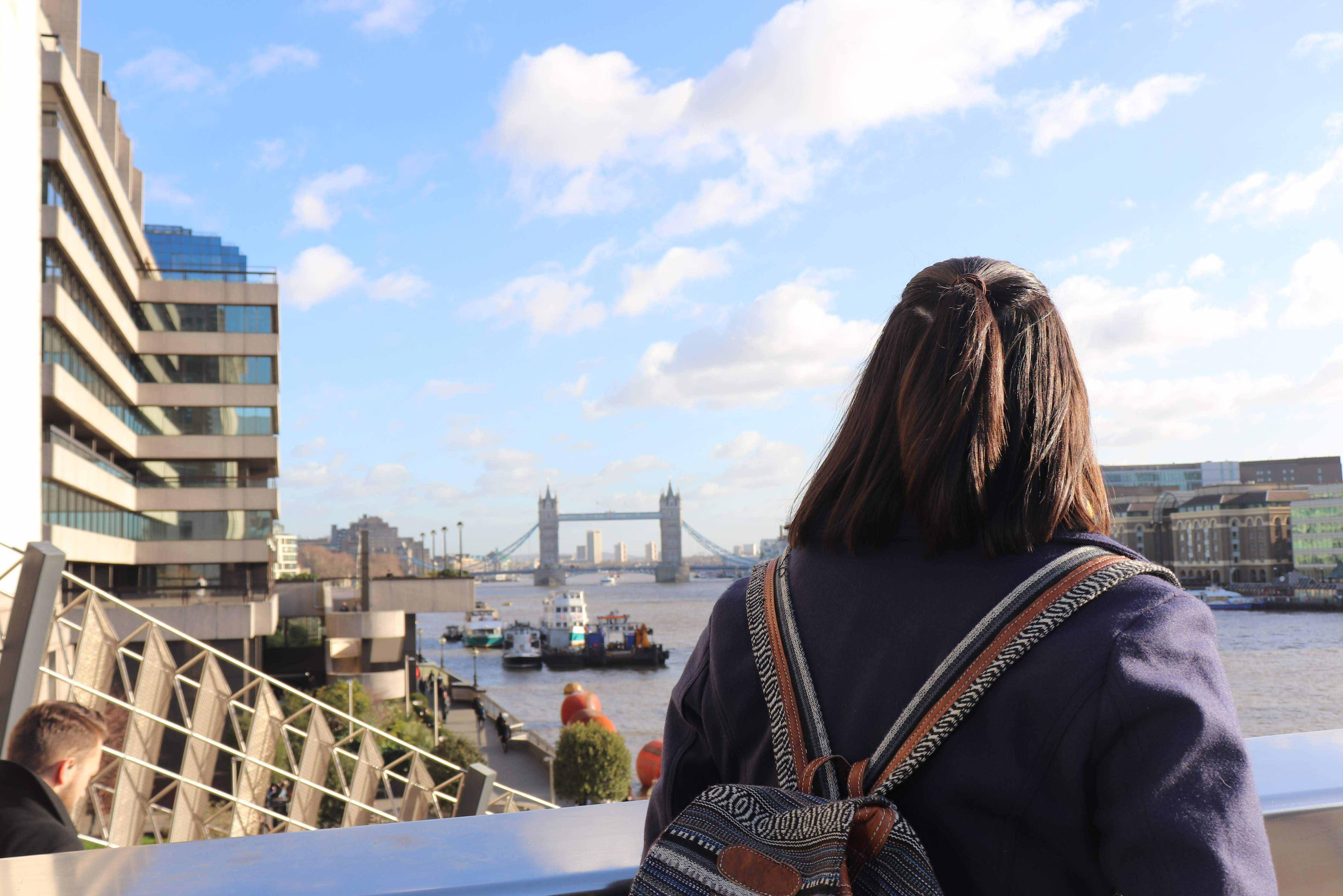 Mia standing looking out at the view from a bridge in London.