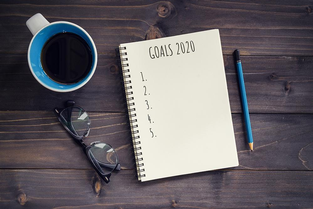 "Notebook with ""Goals 2020"" written at top, with coffee cup and glasses to left"