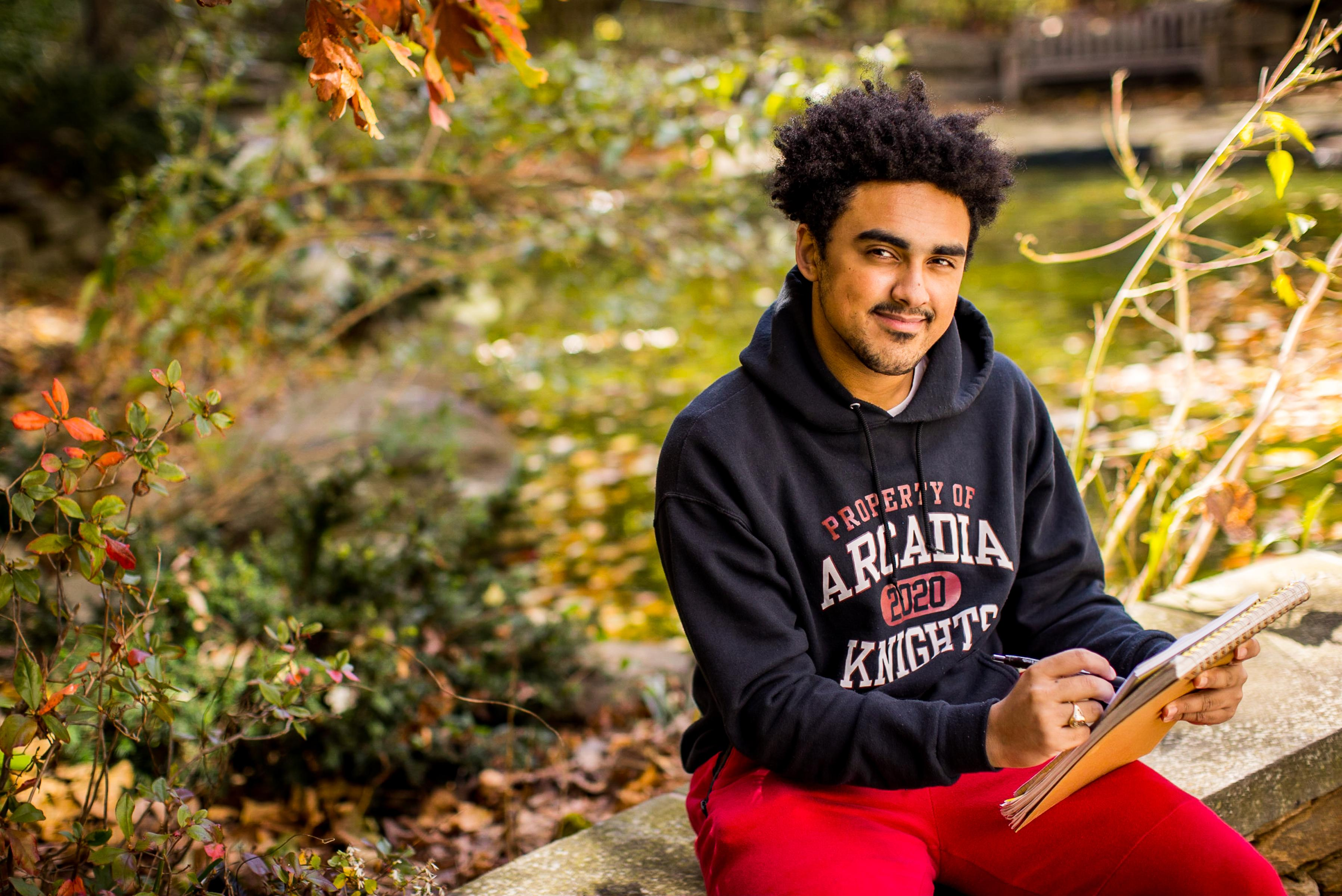 Male Arcadia University student sits at edge of Easton Pond working in notebook