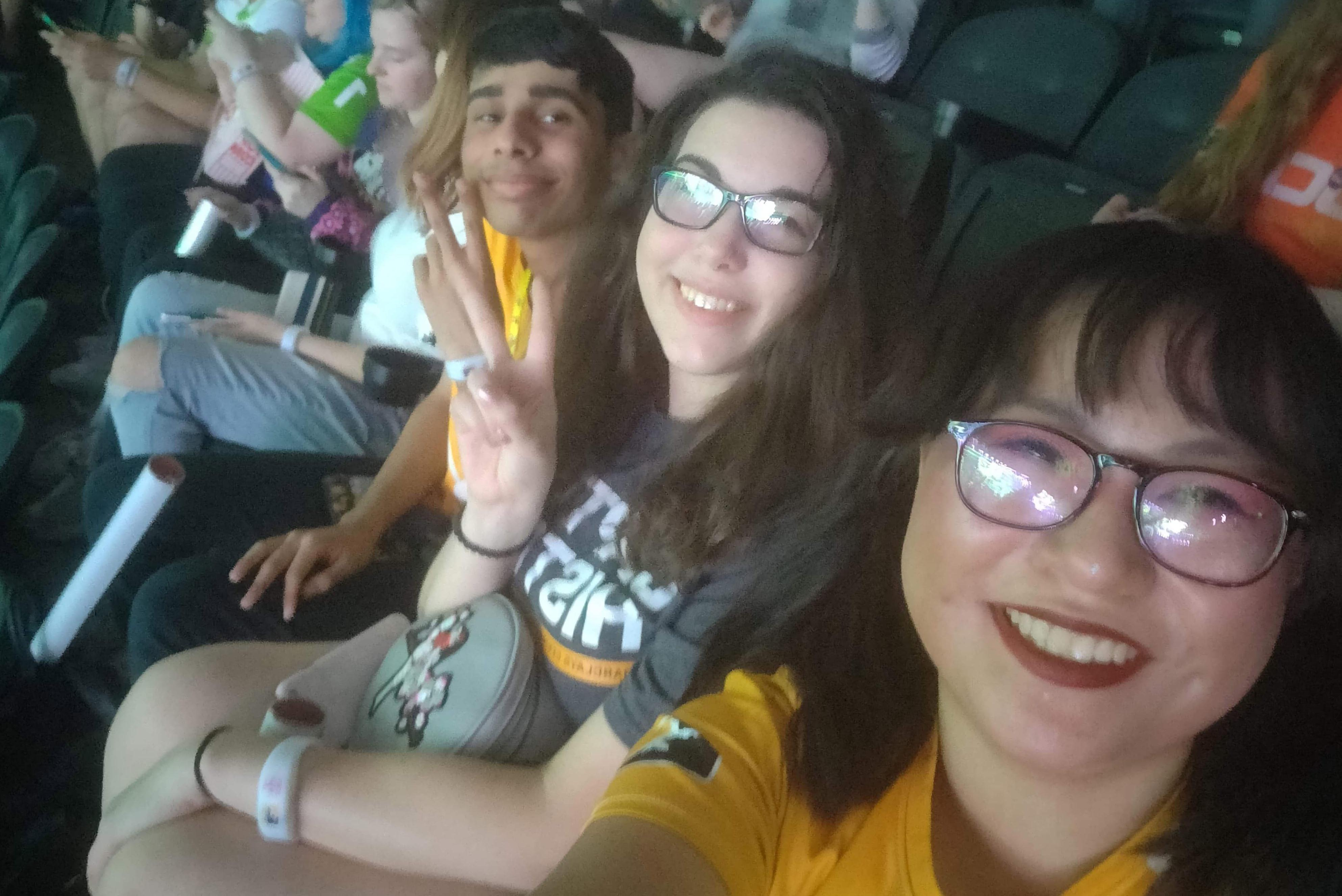 Two female students and one male student sitting in the Wells Fargo Stadium.