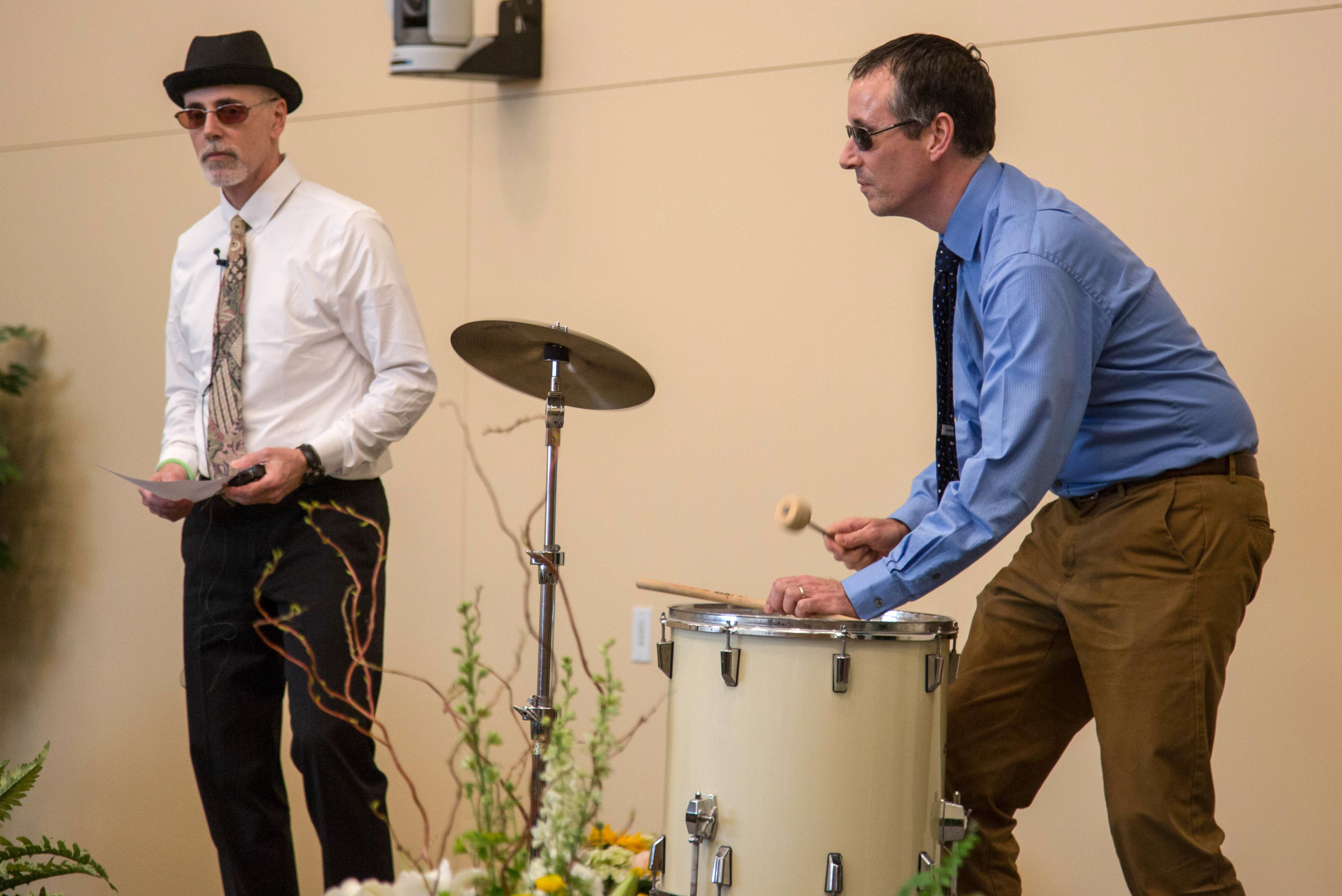Dr. Tevald plays the drum at the PT Pinning ceremony.