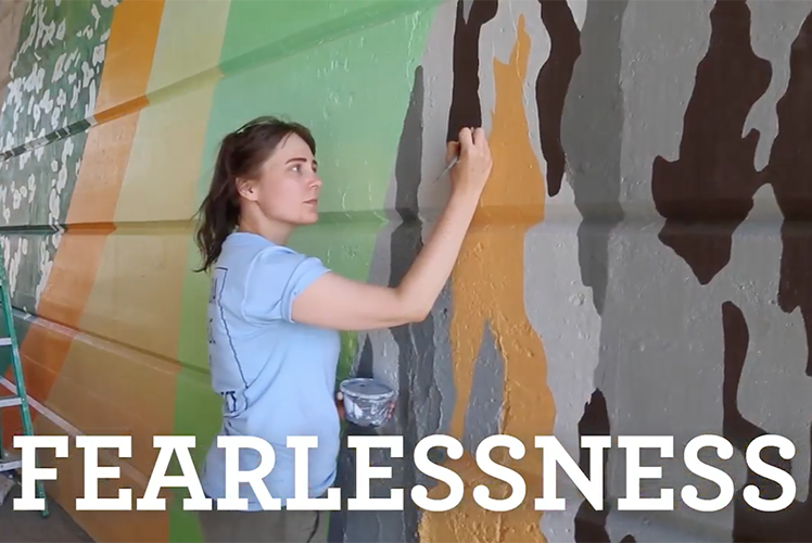 "Student paints mural with ""Fearlessness"" written at bottom"