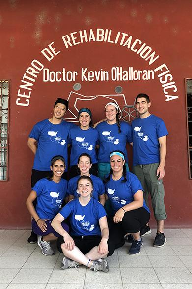 Eight PT students in front of Centro de Rehabilitacion Fisico sign.