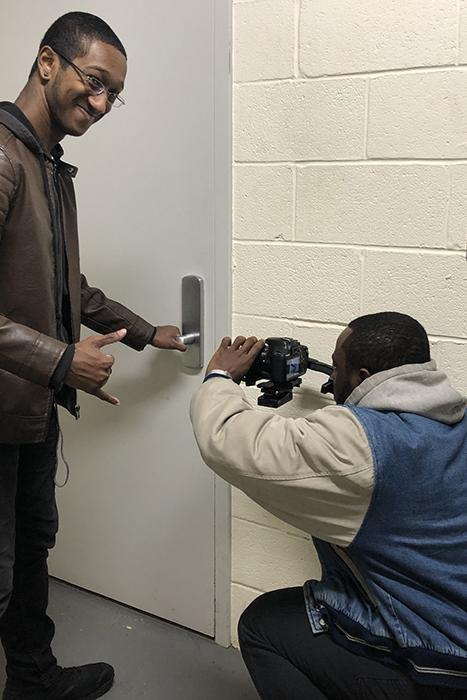 One male student films while another opens a door in a hallway.