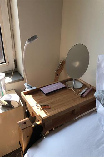 View of a mirror sitting on a bed caddy attached to bedframe.
