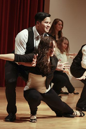 Male and female student do a dip while performing a latin dance on stage.