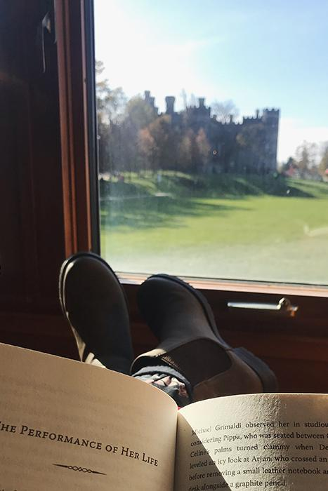 View of feet resting on a window frame while reading a book.