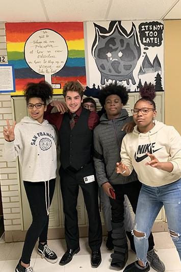 Nicholas Schiavo posing for a photo with 3 students in a hallway.