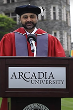 President Nair in graduation regalia at Arcadia podium, castle in background