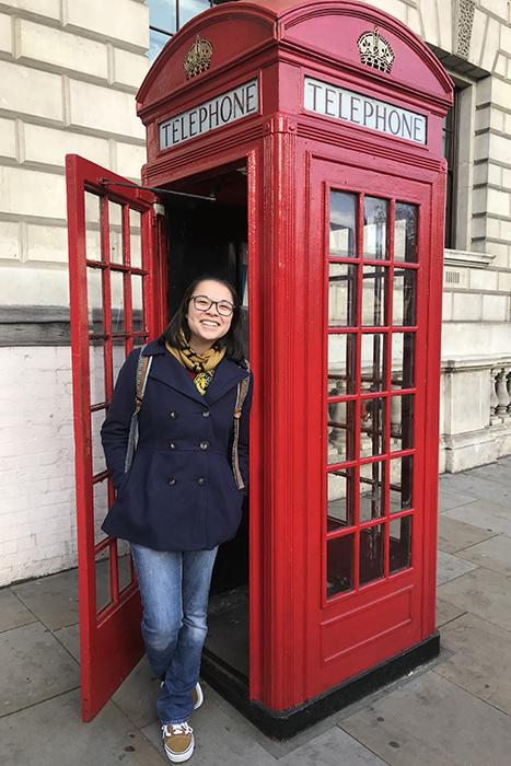 Mia Woo standing in the entrance to a telephone booth in London.