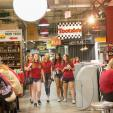 Group of female students smiling as they walk through Reading Terminal Market.