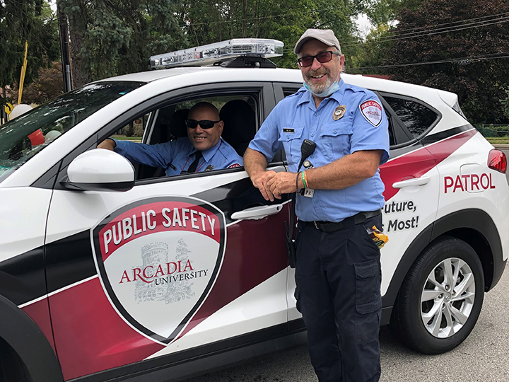 Two public safety officers standing in front of a patrol vehicle smiling