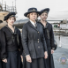 Four women in military outfits with a navy ship behind them
