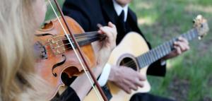 A photo of a woman playing the violin and a man playing the guitar