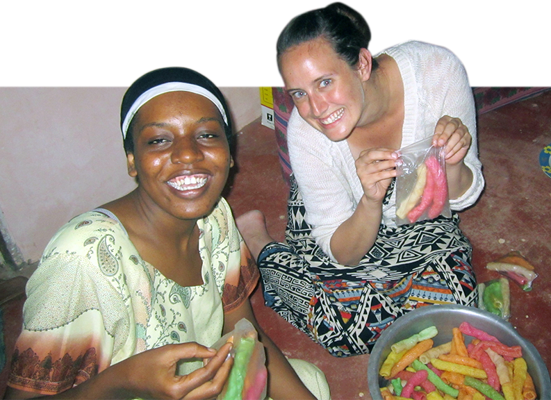 Faculty making candy with African woman.