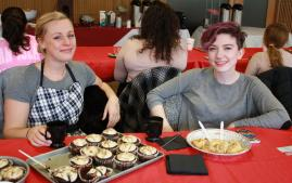 two honors program students with baked goods