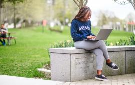 Arcadia University student sitting near Haber Green on her laptop