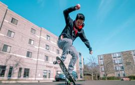 Anthony Carbonetta riding his skateboard on campus