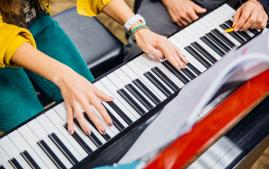 Close up photo of Arcadia University student playing a piano