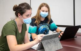 Students on iPads wearing PPE masks
