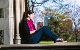Student working on laptop sitting inside castle entryway